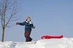 Pojke med den röda plast- pulkan på en snöig kulle royaltyfri fotografi