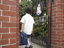 Pojke med den skrivande in skolaporten för ryggsäck Arkivfoton