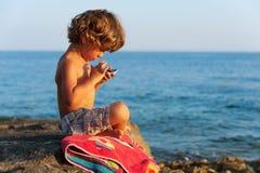 Pojke med den smarta telefonen Fotografering för Bildbyråer