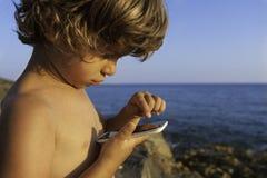Pojke med den smarta telefonen Arkivfoton