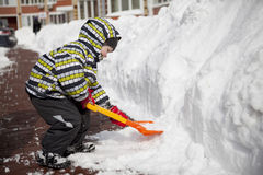 Pojke med den stora skyffeln som gör klar snö Royaltyfria Foton