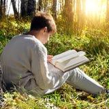 Pojke med den utomhus- boken Fotografering för Bildbyråer