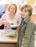 Pojke med det bibliotekarieScanning Books At arkivet arkivbild