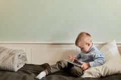 Pojke med digitalt minnestavlasammanträde på soffan, i vardagsrum arkivbilder