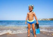 Pojke med dykapparatmaskeringen, skovlar som står på kusten royaltyfri fotografi