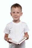 Pojke med en öppen bok som isoleras på en vit Royaltyfria Bilder