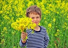 Pojke med en bukett av vildblommor Royaltyfria Foton