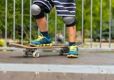 Pojke med en fot på skateboarden överst av rampen Arkivbild