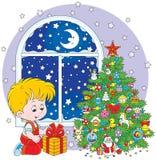 Pojke med en julgåva Arkivfoton