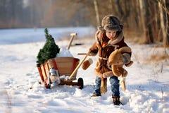 Pojke med en julgran i vinterskogen arkivfoton