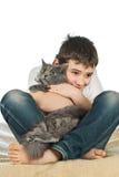 Pojke med en katt på en vit background4 arkivfoton