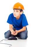 Pojke med en pinne och en hjälm arkivfoto