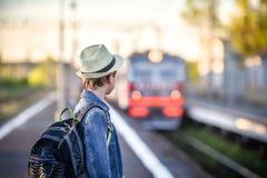 Pojke med en ryggsäck på drevstationen som väntar på drevet Royaltyfri Bild