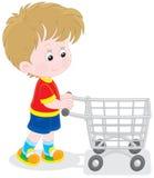 Pojke med en shoppingspårvagn Arkivbild