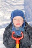 Pojke med en skyffel efter en snönedgång. Arkivbilder