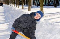 Pojke med en skyffel efter en snönedgång. Arkivfoton