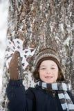 Pojke med en snöflinga Arkivbild