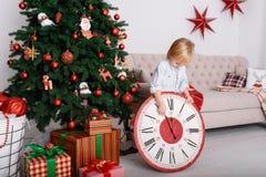 Pojke med en stor klocka i julgran arkivfoton