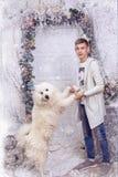 Pojke med en vit hund Arkivbild