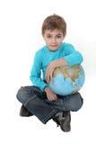 Pojke med ett jordklot i hans varv arkivbild