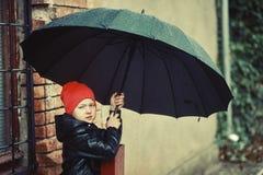Pojke med ett paraply på en gå Arkivbilder