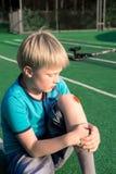 Pojke med ett skrapat knä arkivbilder
