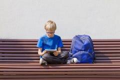 Pojke med exponeringsglas genom att använda minnestavlaPC Barnsammanträde på bänken utomhus- Utrymme för fri kopia Utbildning tek arkivfoto
