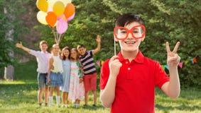 Pojke med exponeringsglas som visar fred på födelsedagpartiet fotografering för bildbyråer