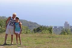 Pojke med farfadern på kullen Arkivbilder