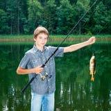 Pojke med fisken Arkivfoto