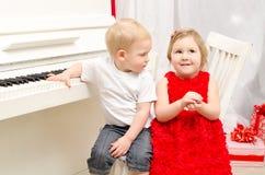 Pojke med flickan som sitter nära det vita pianot royaltyfri fotografi
