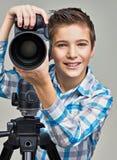 Pojke med fotokameran på thripod Arkivbilder