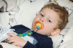 Pojke med fredsmäklaren i säng Royaltyfri Foto