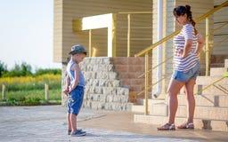 Pojke med glass som grälas på av den ilskna modern Fotografering för Bildbyråer