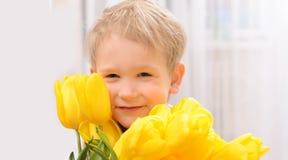 Pojke med gula tulpan Arkivfoton