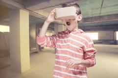Pojke med hörlurar med mikrofon för DIY-virtuell verklighetpapp Arkivbilder