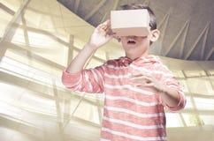 Pojke med hörlurar med mikrofon för DIY-virtuell verklighetpapp Arkivbild