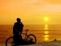 Pojke med hans cykel som vilar och ser havet Arkivbild