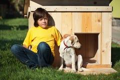 Pojke med hans nya valpsammanträde Royaltyfria Foton