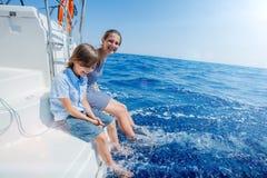 Pojke med hans syster ombord av seglingyachten på sommarkryssning Resa affärsföretaget som seglar med barnet på familjsemester Arkivfoto