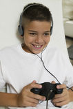 Pojke med hörlurar som spelar videospelet Royaltyfri Fotografi