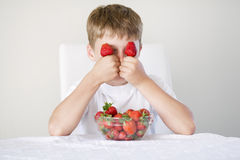Pojke med jordgubbar Arkivbild