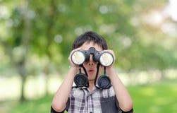 Pojke med kikare i trädgård Royaltyfri Foto