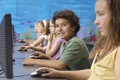 Pojke med klasskompisar i datorlabb Royaltyfria Bilder