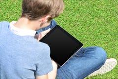 Pojke med korsade ben som utomhus kopplar av Fotografering för Bildbyråer