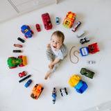 Pojke med leksakbilar Arkivbild