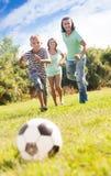 Pojke med lyckliga föräldrar som spelar i fotboll Fotografering för Bildbyråer