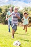 Pojke med lyckliga föräldrar som spelar i fotboll Arkivfoton