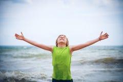 Pojke med lyftta händer på kusten Arkivfoton