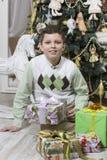 Pojke med många julgåvor Arkivfoton